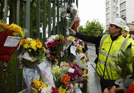 A worker adds flowers to other floral tributes to Drummer Lee Rigby, of the British Army's 2nd Battalion The Royal Regiment of Fusiliers, at