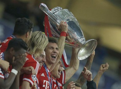 Bayern Munich's Arjen Robben holds the trophy with team mates after defeating Borussia Dortmund in their Champions League Final soccer match