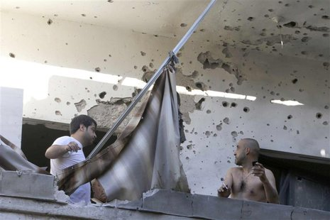 Two men inspect their damage house after two rockets hit their area in a Beirut suburbs May 26, 2013. Two rockets hit a Hezbollah-controlled