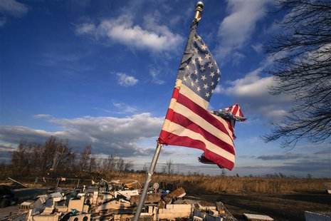 A tattered U.S. flag flies over the foundation of a home destroyed by the storm surge of superstorm Sandy in the Staten Island borough neigh