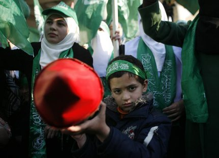 A Palestinian boy poses as he holds a model of rocket during a rally in the West Bank city of Nablus, marking the 25th anniversary of the fo