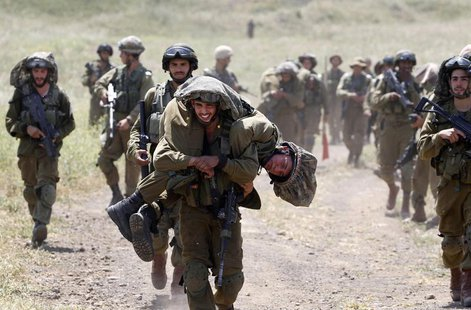 An Israeli soldier carries another soldier as they walk with their comrades during training close to the ceasefire line between Israel and S