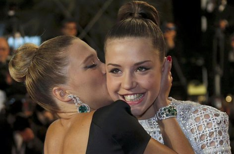 "Cast member Lea Seydoux (L) kisses cast member Adele Exarchopoulos as they pose on the red carpet arriving for the screening of the film ""La"