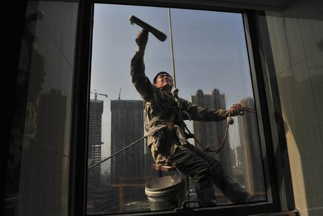 A labourer cleans the window of an office building near a residential complex (back) under construction in Shenyang, Liaoning province May 1