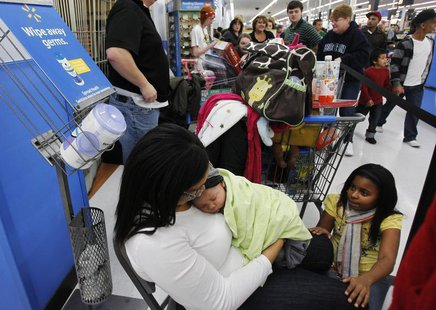 Shawna Ellis (L) cradles her two-month-old son Aiden as she and Tianna Rogers (R), 10, wait in line for a computer to go on sale at WalMart