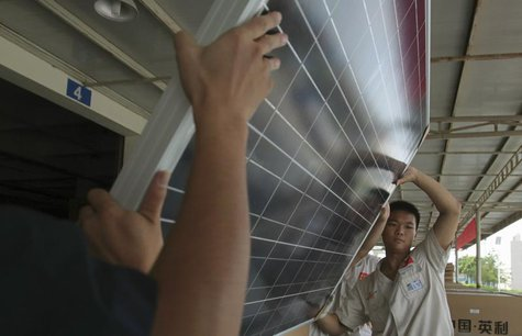 Employees examine newly-made solar panels before boxing for shipment at a factory of Yingli Solar in Baoding, Hebei province August 2, 2012.