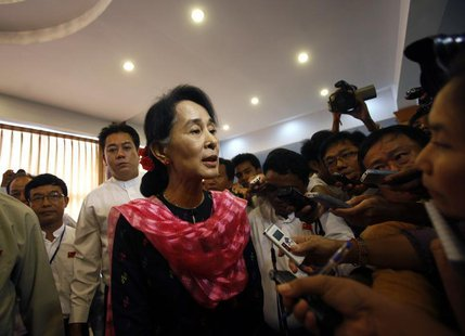 Myanmar pro-democracy leader Aung San Suu Kyi talks to reporters after giving a speech at the first meeting of the central executive committ