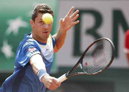 Daniel Brands of Germany hits a return to Rafael Nadal of Spain during their men's singles match at the French Open tennis tournament at the