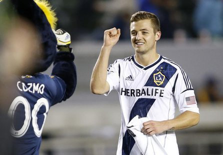 Los Angeles Galaxy midfielder Robbie Rogers (R) fist pumps the team's mascot Cozmo after playing in the second half of the MLS soccer game a