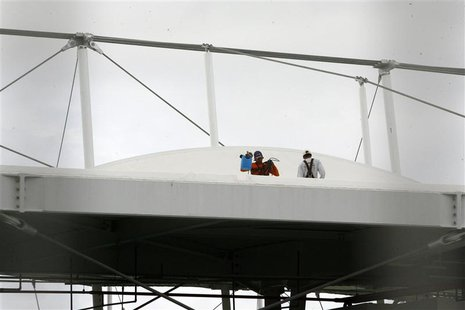Men work on the roof of the Fonte Nova stadium after heavy rain in preparation for the 2013 Confederations Cup, in Salvador May 27, 2013. RE
