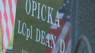 An American flag is reflected on the headstone of Marine Lance Corporal Dean Opicka of Casco on Sunday, May 26, 2013. LCpl. Opicka died in Iraq in 2008. (courtesy of FOX 11).