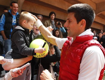 Novak Djokovic of Serbia signs autographs after a training session for the French Open tennis tournament at the Roland Garros stadium in Par