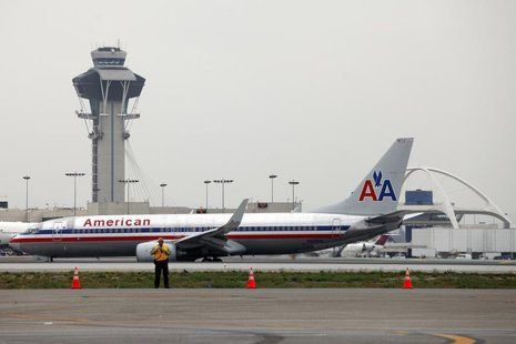 An American Airlines jet passes the Air Traffic Control Tower on the runway at Los Angeles International Airport (LAX), California April 24,