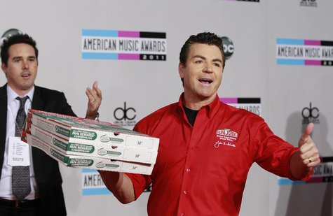 John Schnatter (R), founder and chief executive of Papa John's Pizza, arrives at the 2011 American Music Awards in Los Angeles November 20,