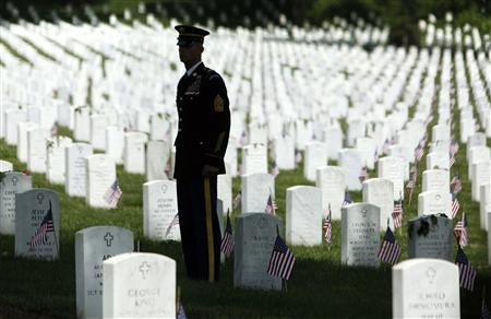 A member of the honor guard stands at attention as U.S. President Barack Obama arrives in his motorcade for Memorial Day observances at Arlington National Cemetery in Arlington, Virginia, May 27, 2013.  REUTERS/Jonathan Ernst