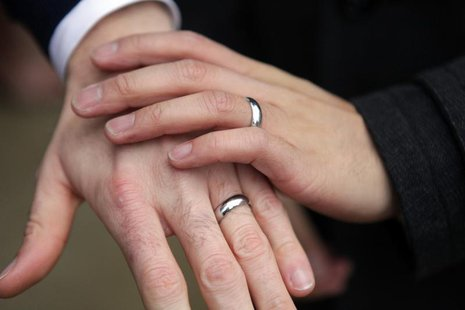 Bernie Liang (L), and Ryan Hamachek, show their rings after getting married outside Seattle City Hall in Seattle, Washington December 9, 201