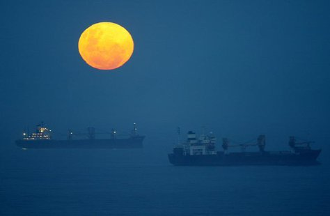 Ships lie at anchor outside the harbour at Durban, South Africa as a full moon rises on Boxing Day December 26, 2004. REUTERS/Howard Burditt