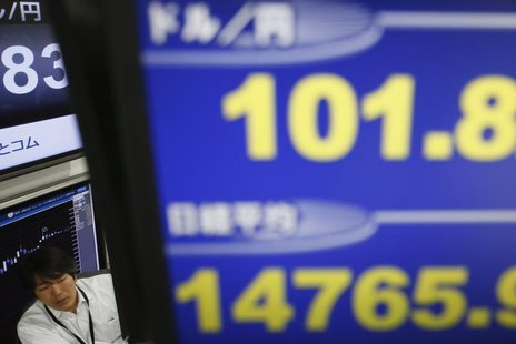 A employee of a foreign exchange trading company is seen between monitors displaying the Japanese yen's exchange rate against the U.S. dolla