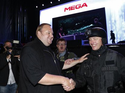 "An actor in police costume greets Megaupload founder Kim Dotcom (L) as he launches his new file sharing site ""Mega"" in Auckland January 20,"