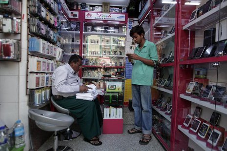A man selling mobile phones, uses his own at a shop in Yangon February 4, 2013. REUTERS/Soe Zeya Tun