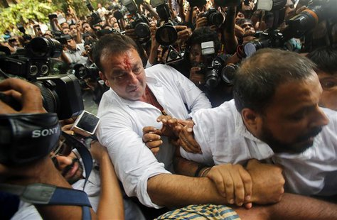 Bollywood actor Sanjay Dutt is escorted by his security staff as he arrives to surrender at a court in Mumbai May 16, 2013. REUTERS/Vivek Pr