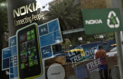 A man is reflected on the glass door of a Nokia showroom in New Delhi March 28, 2013. REUTERS/Mansi Thapliyal
