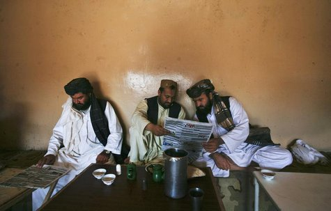 Pashtun men read local newspapers reporting the arrest of senior al Qaeda leader Younis al- Mauritani at roadside tea shop in Quetta Septemb