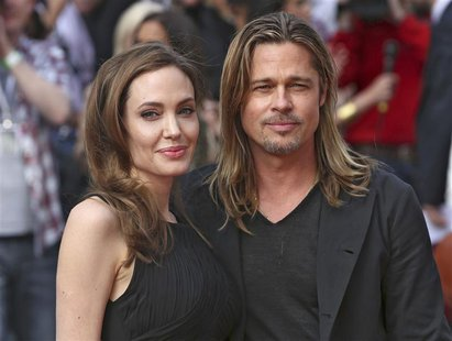 Angelina Jolie poses with her husband Brad Pitt as they arrive for the world premiere of his film World War Z in London June 2, 2013. REUTER