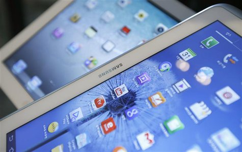 Samsung Electronics' Galaxy Tab (front) and Apple's iPad are seen in this picture illustration taken in Seoul May 13, 2013. REUTERS/Kim Hong