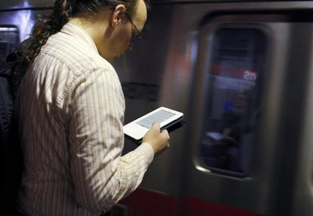 A commuter reads on his Kindle e-reader as a subway train arrives in Cambridge, Massachusetts, March 18, 2011. REUTERS/Brian Snyder