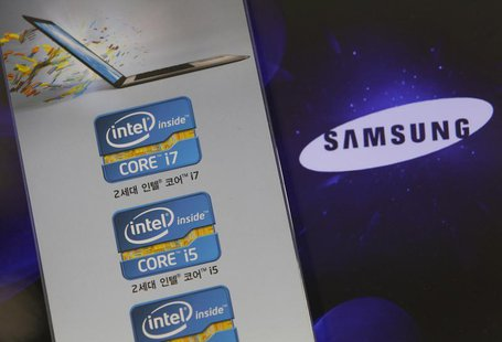 The Samsung Electronics logo is seen on a laptop computer screen (R) in front of an advertisement board promoting Intel processors at a stor