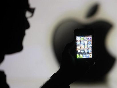 A man is silhouetted against a video screen with an Apple logo as he poses with an Apple iPhone 4 smartphone in this photo illustration take