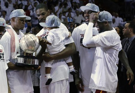 Miami Heat's Dwyane Wade (R), LeBron James (2nd R), Chris Bosh (back C) and his son Jackson look on as Ray Allen holds the Eastern Conferenc
