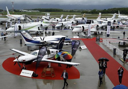 Visitors walk past aircrafts in the static display area during the Annual European Business Aviation Convention & Exhibition (EBACE) at Coin