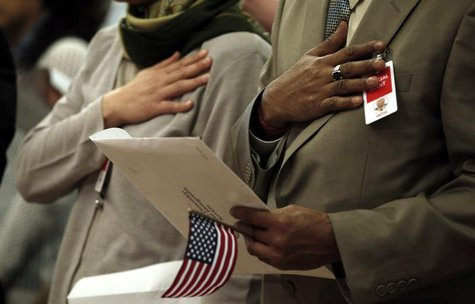 Immigrants put their hands to their hearts as the national anthem is played during a special naturalization ceremony at the Department of Ju