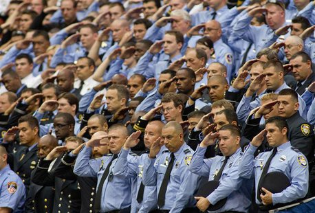 Firefighters stand and salute during a memorial service for four Houston firefighters in Houston, Texas June 5, 2013. REUTERS/Richard Carson