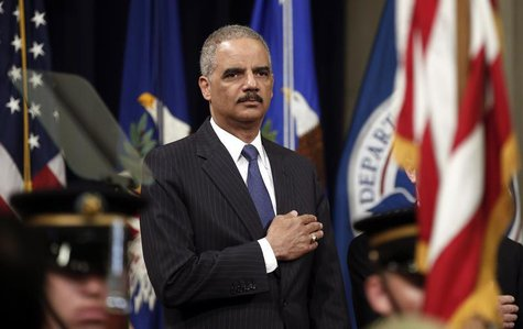U.S. Attorney General Eric Holder puts his hand to his heart during the national anthem as he hosts a special naturalization ceremony at the