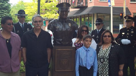 The new statue surrounded by members of the Zapata family, who are surrounded by the Public Safety Department's Honor Guard.