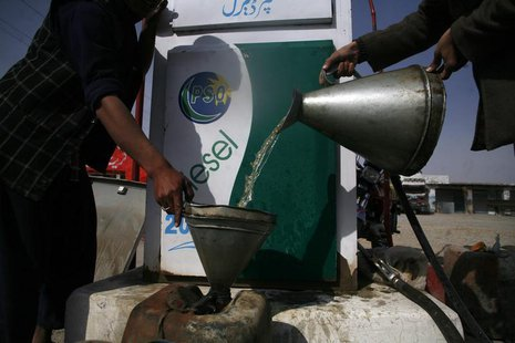 A man fills a canister with petrol that he says was brought from Iran, at a roadside petrol station on the outskirts of Quetta February 13,