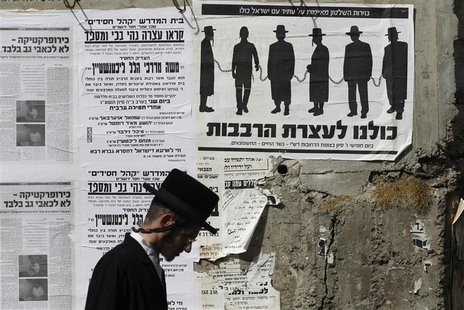 An ultra-Orthodox Jewish man walks past a street poster in Jerusalem's Mea Shearim neighbourhood, inviting the public to a protest against g