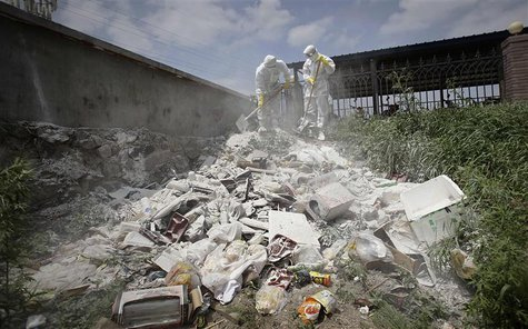 Health officers sterilize a dump site with lime powder, near the site of a poultry slaughterhouse fire in Dehui, Jilin province June 6, 2013