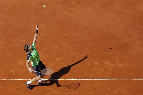 David Ferrer of Spain serves to compatriot Tommy Robredo during their men's singles quarter-final match at the French Open tennis tournament