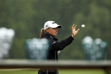 Stacy Lewis of the U.S. catches a golf ball as she warms up in the rain before round one of the LPGA Golf Championship in Pittsford, New Yor
