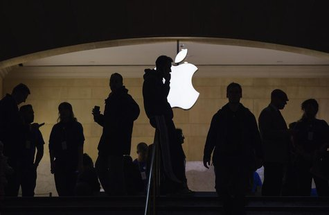 A man talks on his telephone as customers walk through an Apple store in Grand Central Terminal in New York, March 15, 2013. REUTERS/Lucas J