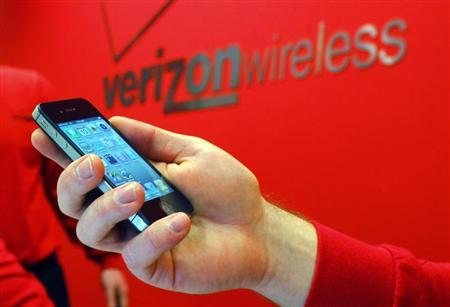 An employee holds out an iPhone for a customer at a Verizon store in Boston, Massachusetts February 10, 2011. Credit: Reuters/Brian Snyder