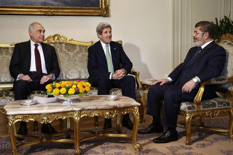 Egyptian Foreign Minister Mohammed Kamel Amr (L), sits with U.S. Secretary of State John Kerry, and Egyptian President Mohamed Mursi (R) dur