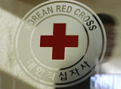 A man walks past a logo of the South Korean Red Cross at its headquarters in Seoul February 9, 2011. REUTERS/Truth Leem