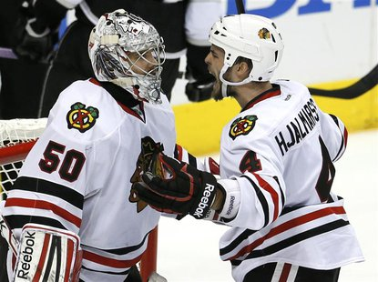 Chicago Blackhawks defenseman Niklas Hjalmarsson (4) celebrates with goalie Corey Crawford (50) after defeating the Los Angeles Kings in Gam