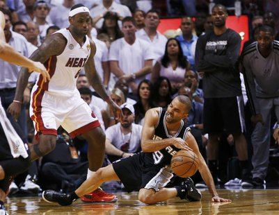 San Antonio Spurs' Tony Parker slips while being guarded by Miami Heat's LeBron James (L) during the fourth quarter in Game 1 of their NBA F