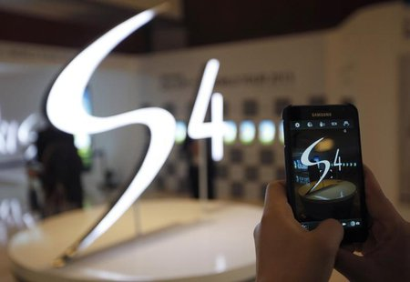 A man takes a photograph of a logo of Samsung Electronics Co Ltd's latest flagship smartphone S4 during its launch event at the company's he